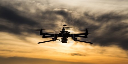 Photo for Professional drone flying in the sunset with dark clouds - Royalty Free Image