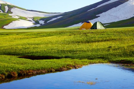 two tents in mountains at a sunset