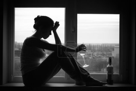 Woman in depressed mood sits on the window