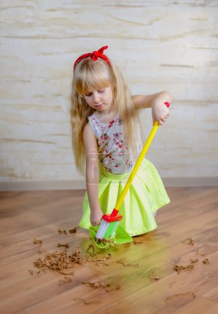 Pretty little blond girl cleaning the house