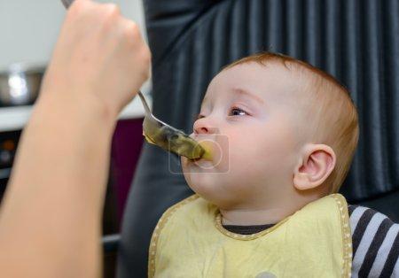 Cute Baby Boy on Chair Eating Healthy Food