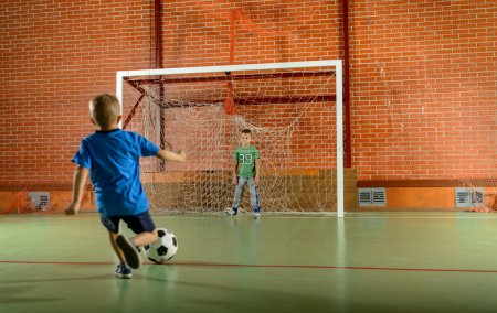 Two young boys playing soccer on an indoor court