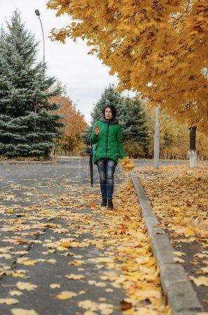 Single woman walking on sidewalk with leaves