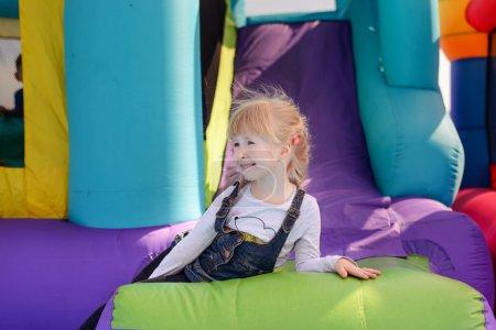 Cute little fair haired girl on a bouncy castle