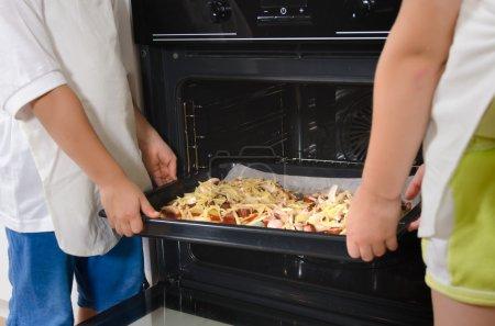 Dos niños colocando pizzas caseras en el horno