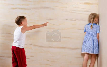 Photo for Two Cute White Kids Playing Hide and Seek Isolated on Light Brown Wooden Walls - Royalty Free Image
