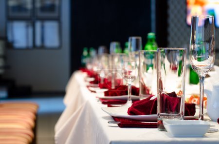 Photo for Formal stylish setting on a dinner table with elegant glassware and red linen for a party or celebration of a special event - Royalty Free Image