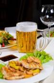 Džbánek piva uprostřed pozlacené nádobí na stole