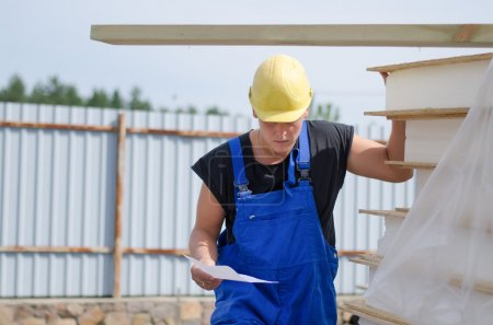 Photo pour Worried builder in his hardhat and overalls on site with a document in his hand looking at a stack of building materials - image libre de droit