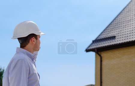 Photo pour Engineer, architect or building inspector standing in his hardhat checking a roof on a new build house against a blue sky - image libre de droit