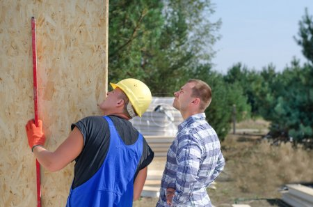 Photo pour Builder and engineer checking a wooden wall panel using a level to see that it is in a vertical position on a residential building site - image libre de droit
