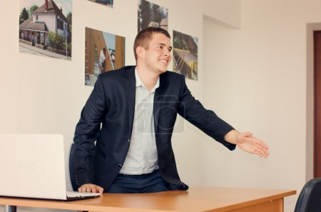 Businessman standing up to shake hands