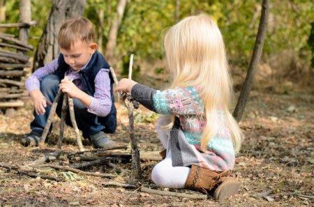 Photo pour Petit garçon et fille élégantjouant dans la forêt avec des bâtons heureusement accroupis ensemble sur le bâtiment de sol différentes structures - image libre de droit