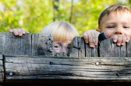 Two children peeking over a wooden fence