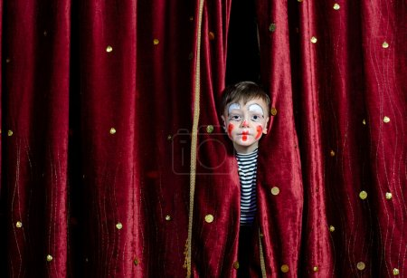Photo pour Young Boy Wearing Clown Make Up Peering Out Through Opening in Red Stage Curtains - image libre de droit