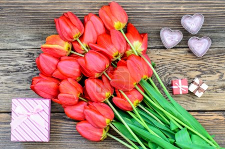 Photo for Bouquet of fresh colorful red tulips with a decorative gift lying on a rustic wooden background symbolic of an anniversary, Valentines Day and love, overhead view - Royalty Free Image