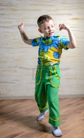 Photo pour Young Boy Wearing Green Pants and Floral Print Shirt Snapping Fingers and Performing Traditional Dance in Studio - image libre de droit