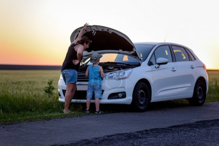 Photo for Rear View of a Mother and Son Repairing Something on their White Car at the Grassy Street Side on One Afternoon. - Royalty Free Image