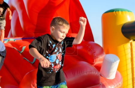 Blond boy playing in red bouncy castle