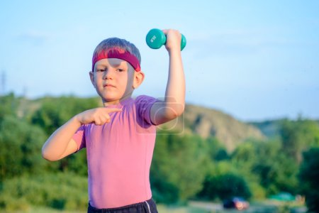 Boy Lifting Dumbbell and Pointing his Arm Muscles