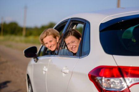 Two happy smiling women in a car