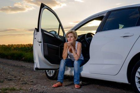 Photo pour Femme assise à attendre l'assistance routière dans la porte ouverte de sa voiture garée sur une route rurale au coucher du soleil regardant fixement devant elle - image libre de droit