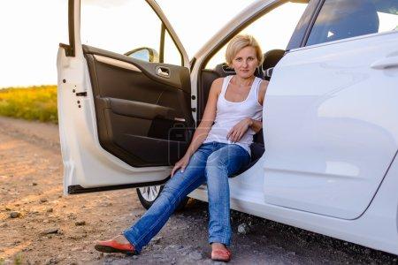 Smiling woman sitting in the open door of her car