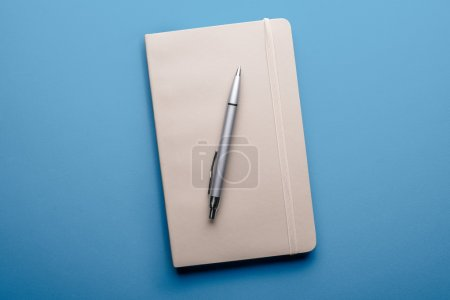 Top view of blank notebook with pen on blue background