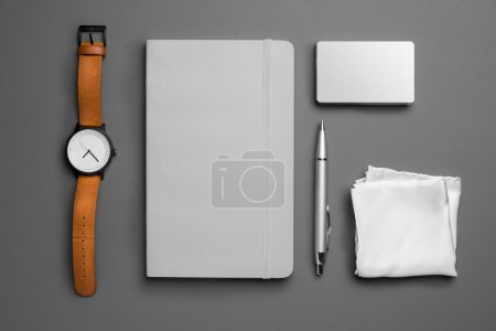 top view of watch and notebook with pen on grey background