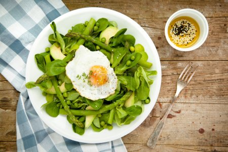 Photo for Healthy spring green salad with egg served on white plate - Royalty Free Image