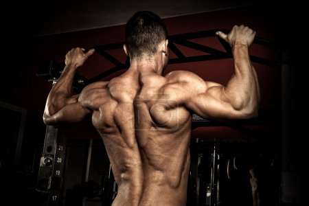 Photo for Strong bodybuilder in the gym doing pull ups - Royalty Free Image