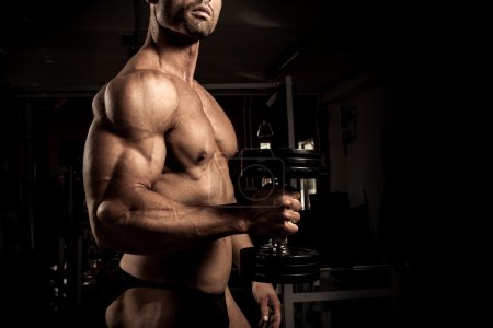 Photo for Strong bodybuilder with dumbbell in the gym - Royalty Free Image