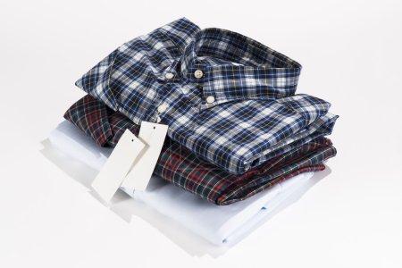 Photo pour Pile des chemises pliées avec l'étiquette blanche - image libre de droit