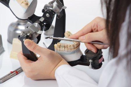 Photo pour Technicien dentaire travaillant avec un articulateur dans un laboratoire dentaire - image libre de droit
