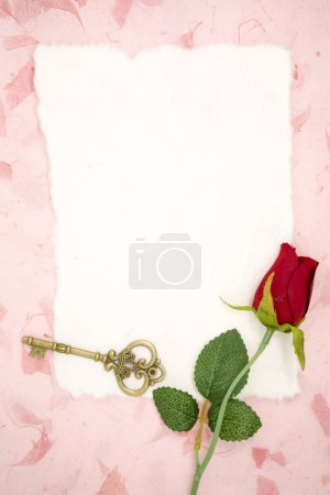 Blank paper with red rose and old key