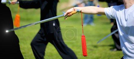 Photo pour Tai Chi athlète d'arts martiaux expert fait des mouvements avec épée tranchante - image libre de droit