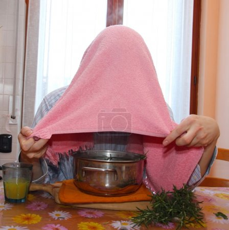man with towel breathe balsam vapors to treat colds