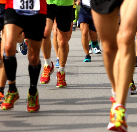 Photo for Athletic and muscular legs of athletes during the race - Royalty Free Image