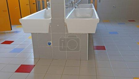 Photo pour À l'intérieur de la salle de bain de l'école maternelle avec lavabos - image libre de droit