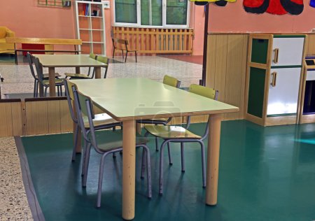 Foto de Table and chairs in the class room of the nursery with a big mirror on the wall - Imagen libre de derechos