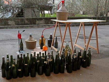 Photo for Pour red wine from the demijohn to glass bottles at home - Royalty Free Image