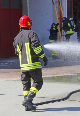 Firefighter sprays water with the spear fighting during the exer