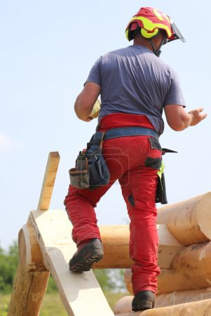 Carpenter with helmet and protective equipment to work safely on