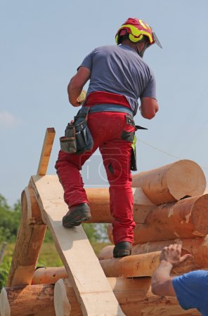 Carpenter with helmet and protective equipment to work safely