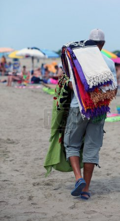 African peddler of towels and beach towels on the beach