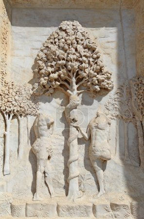 Statues of Adam and Eve with Apple tree in the facade of Abbey C