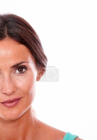 Photo pour Attrayant sourire brune jeune femme ne regardant que la caméra montrant le côté gauche de son visage avec de longs cheveux bruns qui est attaché dos isolé - image libre de droit