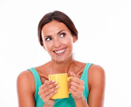 Photo pour Femme de brunette riantre retenant la tasse de café avec les deux mains tout en regardant loin utilisant un dessus vert de réservoir et ses longs cheveux attachés en arrière d'isolement - image libre de droit