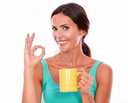 Photo pour Femme de brunette célébrant avec la tasse de café regardant l'appareil-photo gesticulant un signe parfait utilisant un dessus vert de réservoir et ses longs cheveux attachés en arrière d'isolement - image libre de droit