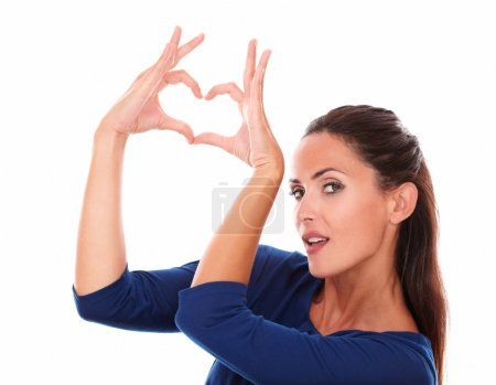 Photo for Charming woman making a love sign with hands while looking at you in white background - copyspace - Royalty Free Image